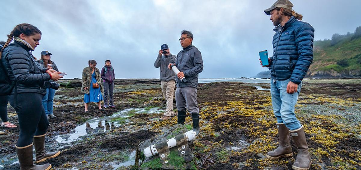 Francis Chan stands in tide pool on the Oregon Coast, with ocean sensor in foreground and a group of people gathered around.