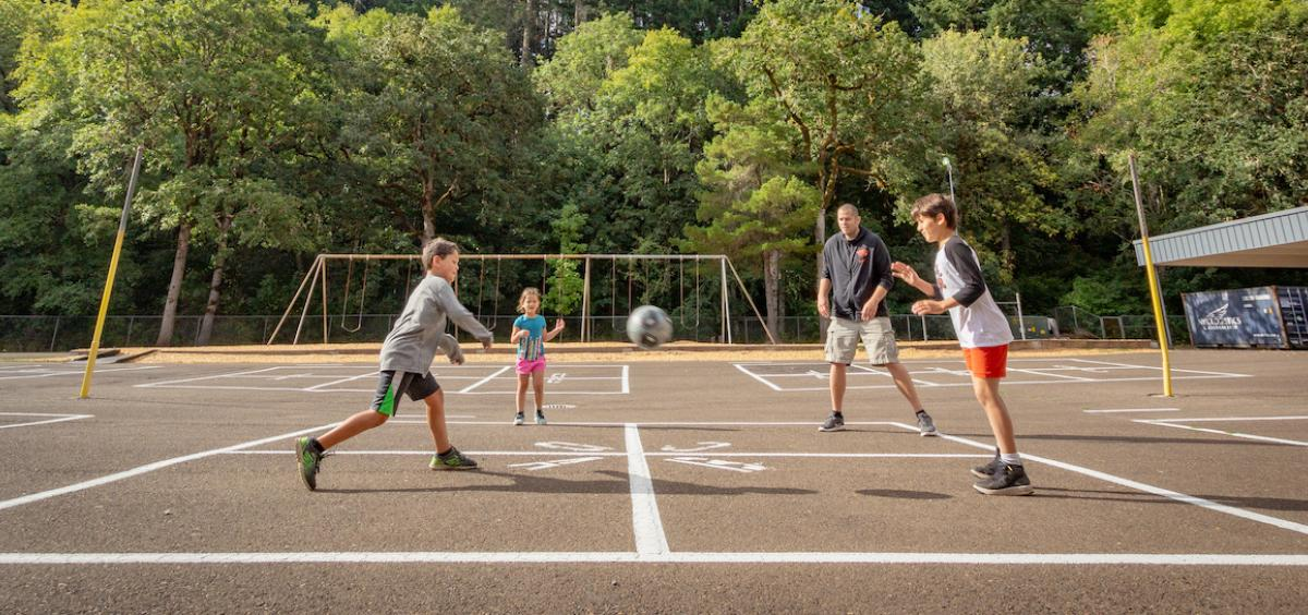 Kids and adult playing four-square on a blacktop playground