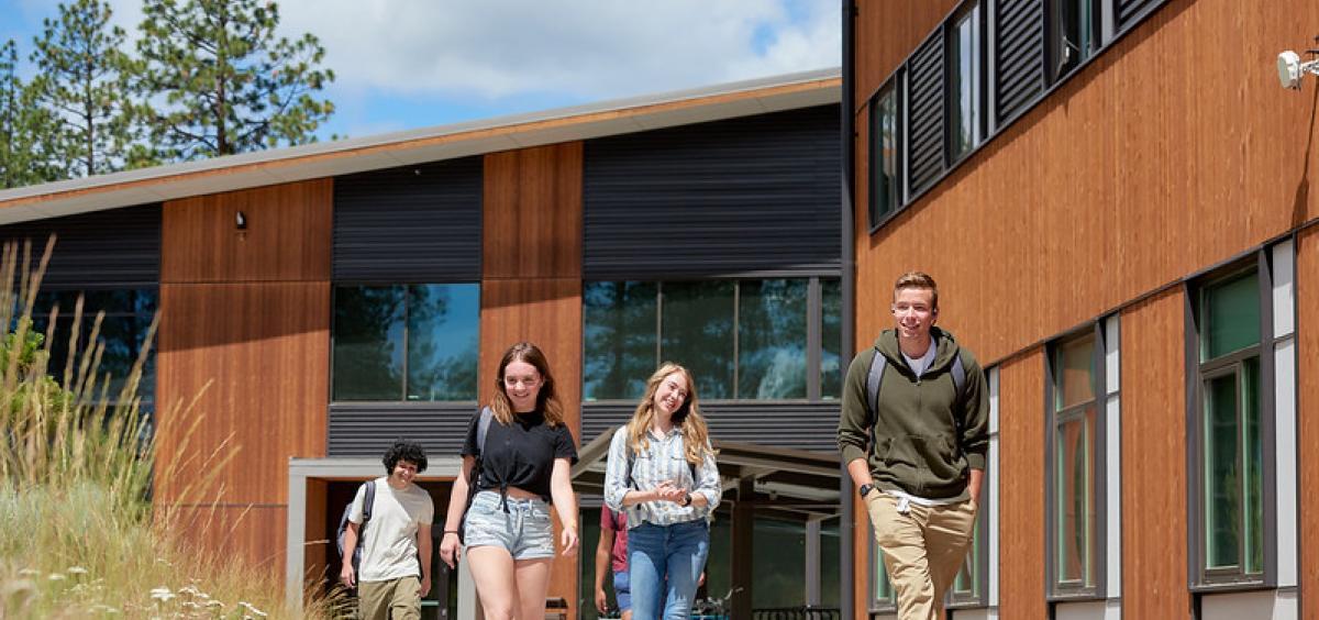Students walk on the sidewalk outside a building at OSU-Cascades.