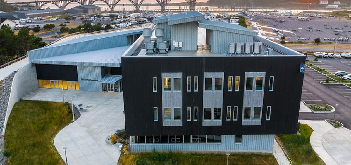 Image of an aerial view of the Gladys Valley Marine Studies Building with the Yaquina Bay Bridge in the background.