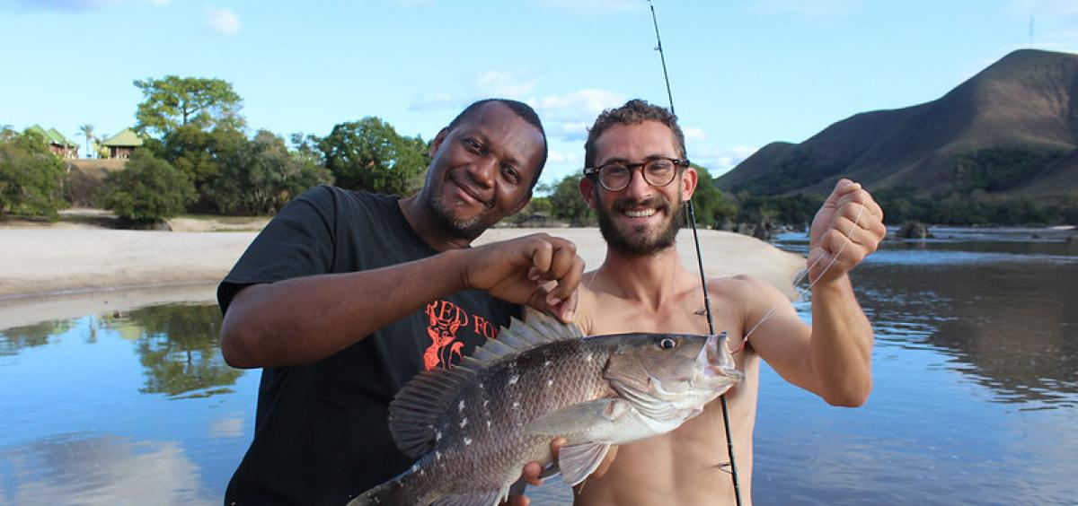 Researcher Joe Cutler (right) poses with a Guinea snapper he collected at Lope National Park in Gabon. This fish was collected farther upstream than any other marine-associated fishes. in Gabon.