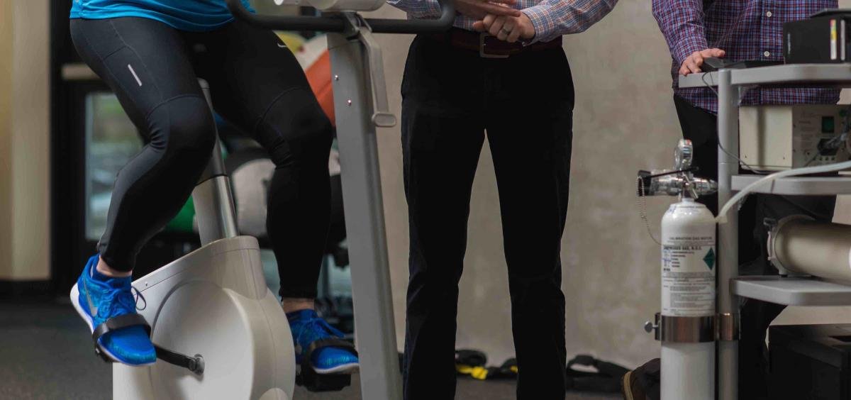 Image of a woman waist-down riding an exercise bike while two researchers stand nearby