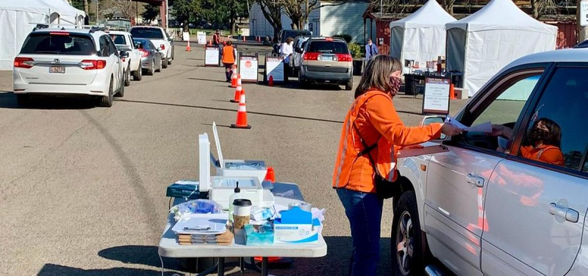 Jan Williams, with the OSU Extension Service in Clackamas County, collects paperwork from participants before they receive their shot at the drive-through COVID-19 vaccination clinic on March 31 in Canby.