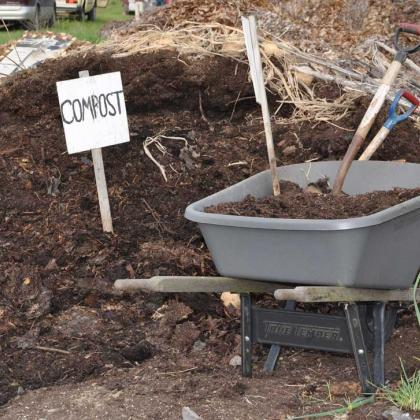Compost pile with wheelbarrow
