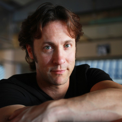 Headshot of David Eagleman, who looks straight at the camera over his arms folded in front of him