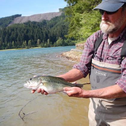 Randy Wildman holds a largemouth bass he caught in Fall Creek Reservoir