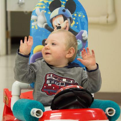 A child raises both hands in the air while sitting in a Go Baby Go car