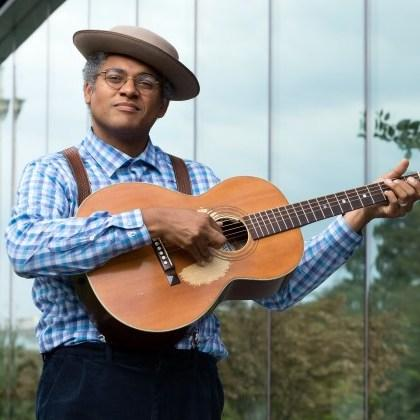 Musician Dom Flemons with his guitar