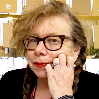 Headshot of Lynda Barry, wearing glasses, red lipstick & hair in two braids.