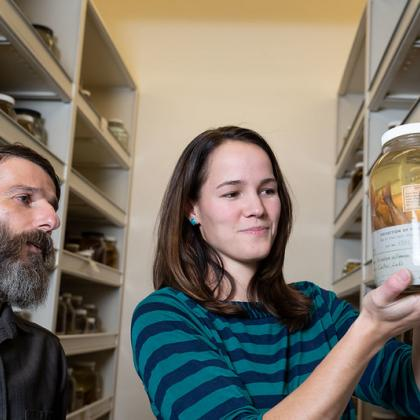 Peter Konstantinidis (left), Oregon State University instructor and curator of the Oregon State Ichthyology Collection, and student Kelci Pauk, look at a preserved whitefish