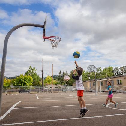 Kids playing basketball on a blacktop playground