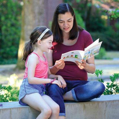 Shauna Tominey reading a book with a child