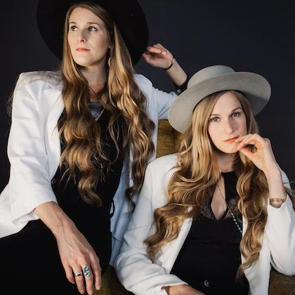 Image of Shook Twins, seated side by side against a black backdrop