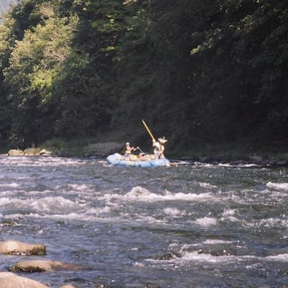Researchers on a raft testing water quality in a river
