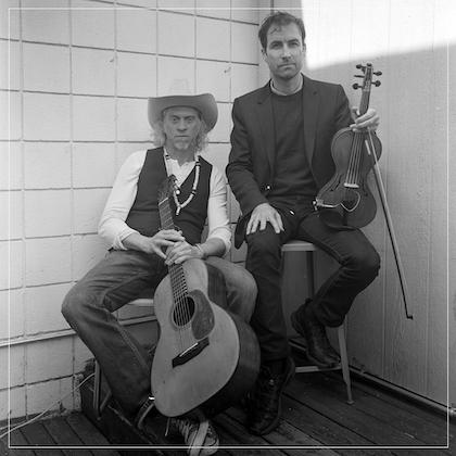 Black & white image of musicians Jimbo Mathus and Andrew Bird; Mathus leans back in his chair, holding a guitar between his legs, while Bird sits on a taller stool, resting a violin upright on his thigh.