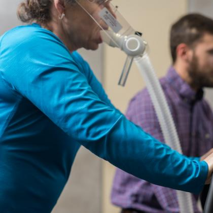 Image of a woman with an plastic mask on her face & tube extending from it while she rides an exercise bike
